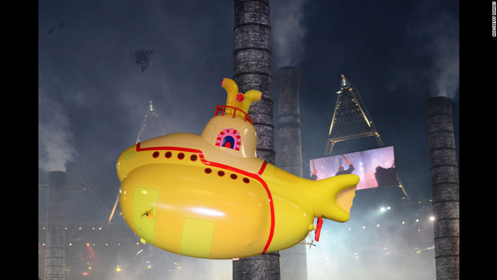 An inflatable yellow submarine floats above artists.