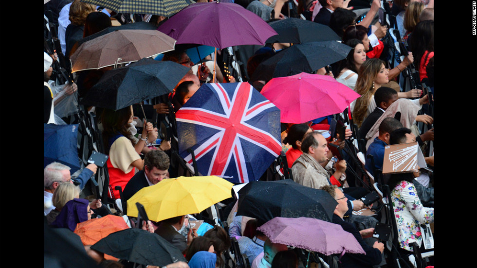 Spectators wait under the rain before the ceremony.