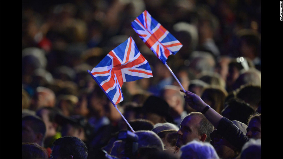 People wave Union flags during the opening ceremony.