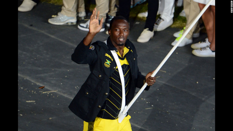 Reigning Olympic men's 100-meter and 200-meter champion Usain Bolt of Jamaica carries his country's flag.