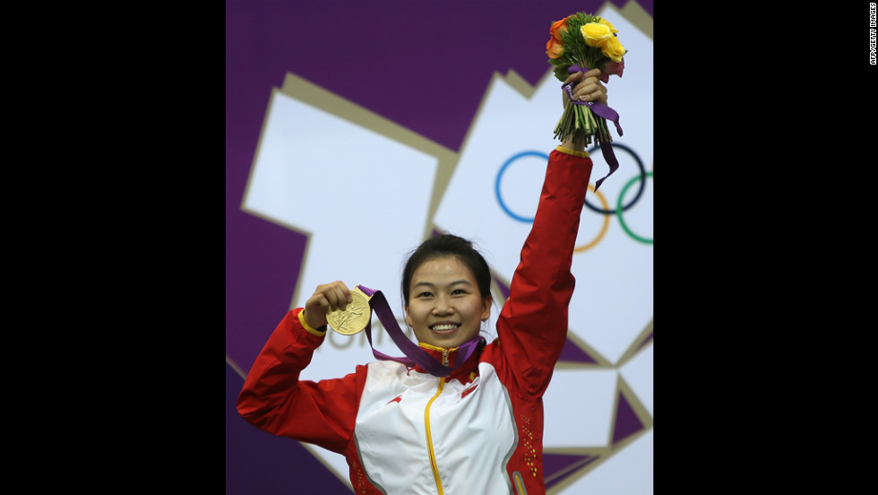 China's Yi Siling celebrates with her gold medal on the podium after winning the 10-meter air rifle women's final.