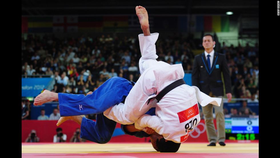 Felipe Kitadai of Brazil, in blue, competes with Rishod Sobirov of Uzbekistan in a judo match.