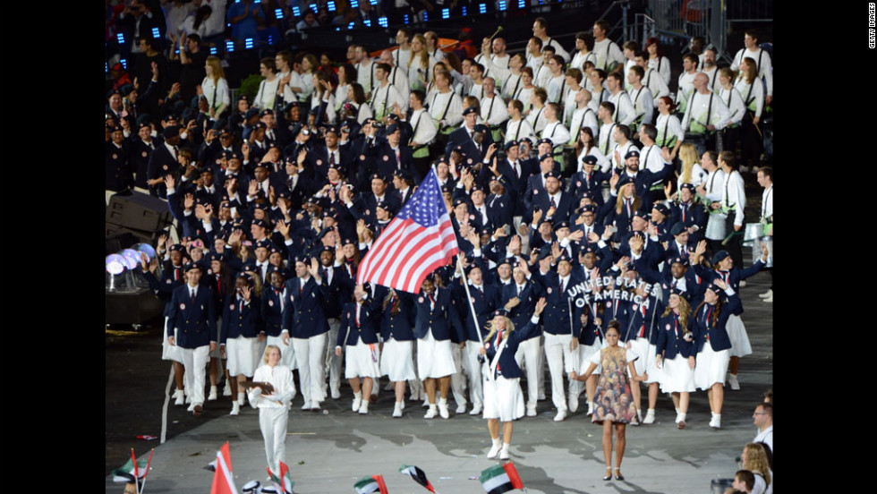 Mariel Zagunis of the American fencing team carries her country's flag.