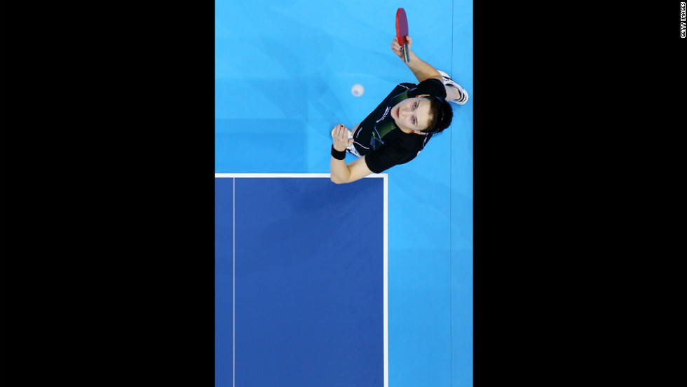 Aleksandra Privalova of Belarus serves against Xing Han of Congo during their women's singles table tennis match.