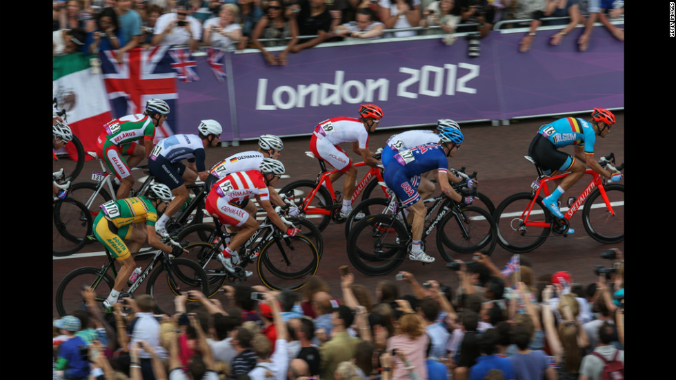 Great Britain's Mark Cavendish, third left, and other competitors approach the last bend of the race outside of Buckingham Palace during the men's cycling road race.