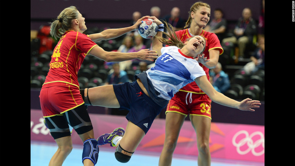 Britain's leftback Ewa Palies, center, vies with Montenegro's Maja Savic, left, and Katarina Bulatovic during a women's preliminary handball match.