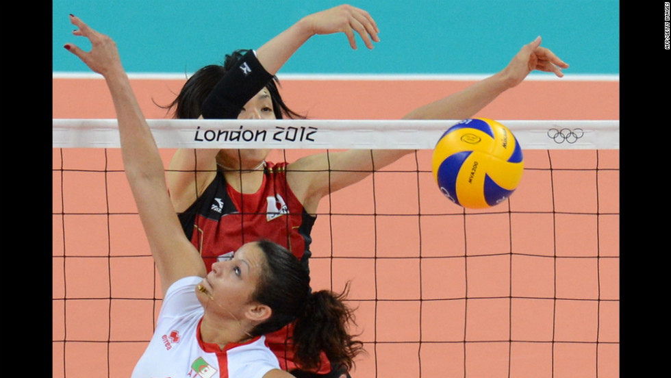 Algeria's Sehryne Hennaoui spikes the ball as Japan's Yukiko Ebata reaches to block during a women's volleyball match.