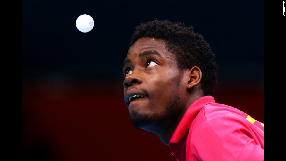 Mawussi Agbetoglo of Togo serves against Justin Han of Australia during their preliminary round singles match in the table tennis competition.