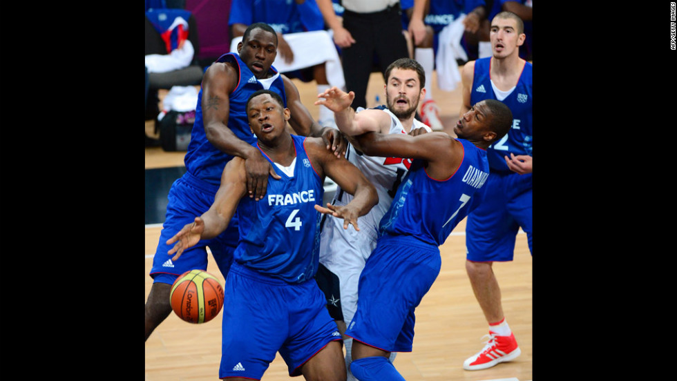 French center Kevin Seraphin, No. 4 in blue, fends off a challenger during the U.S.-France preliminary round match.