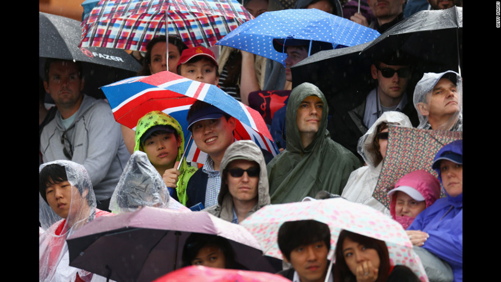 Fan shield themselves from the rain during the women's team archery event at Lord's Cricket Ground in London.