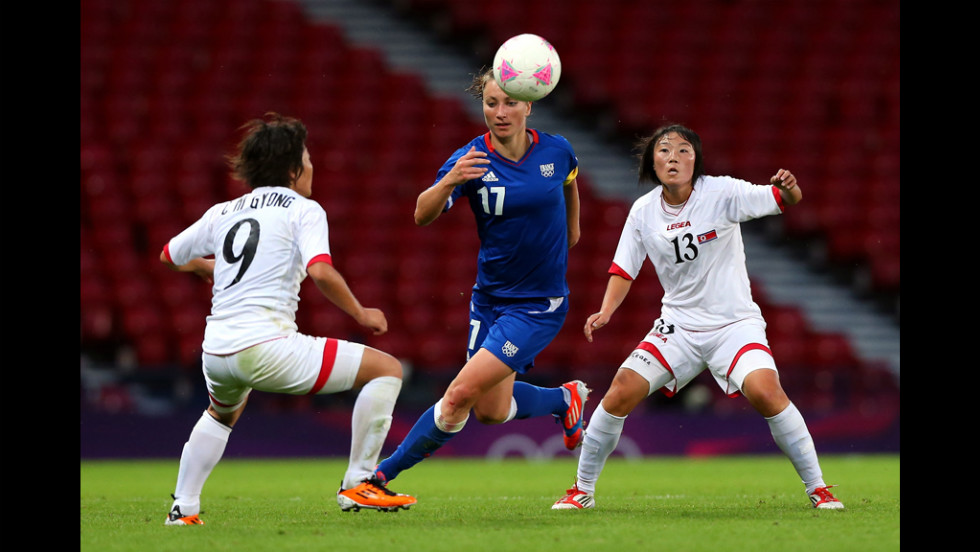 Gaetane Thiney of France is checked by Choe Mi Gyong, left, and O Hui Sun, right, of North Korea during a women's soccer first-round match.