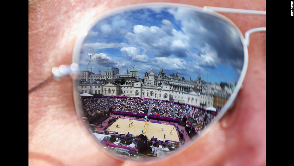 The beach volleyball center court is reflected in the sunglasses of a spectator on Monday.