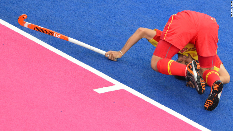 Spain's Jose Ballbe struggles to plant himself during a field hockey match.