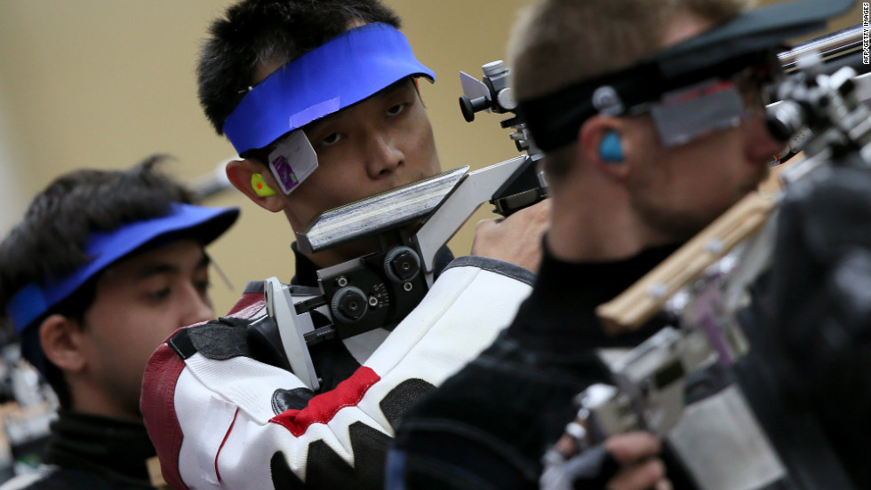 China's Zhu Qinan, center, competes in the men's 10-meter air rifle qualifying round at the Royal Artillery Barracks in London on Monday.