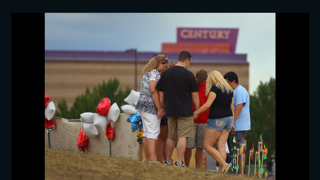 AURORA, CO - JULY 28: Visitors pray together around a cross erected at a memorial setup across the street from the Century 16 movie theatre on July 28, 2012 in Aurora, Colorado. Twenty-four-year-old James Holmes is suspected of killing 12 and injuring 58 others July 20 during a shooting rampage at a screening of 'The Dark Knight Rises' in Aurora, Colorado.(Photo by Joe Raedle/Getty Images)
