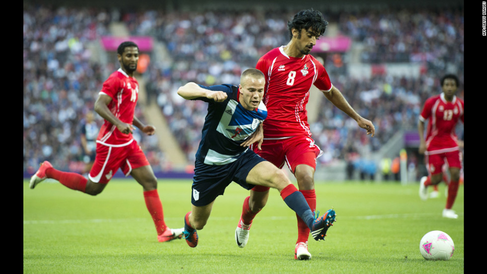 Britain's Tom Cleverley, center, vies for the ball with United Arab Emirate's Hamdan Al-Kamali, right.