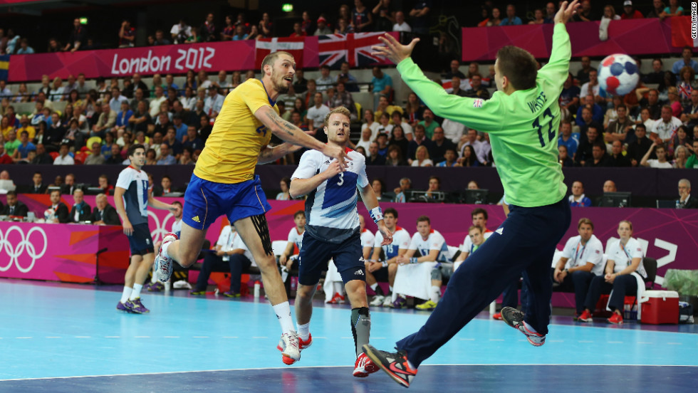 Sweden's Fredrik Petersen scores on Robert White of Great Britain during the men's handball preliminary match between Britain and Sweden on Tuesday.