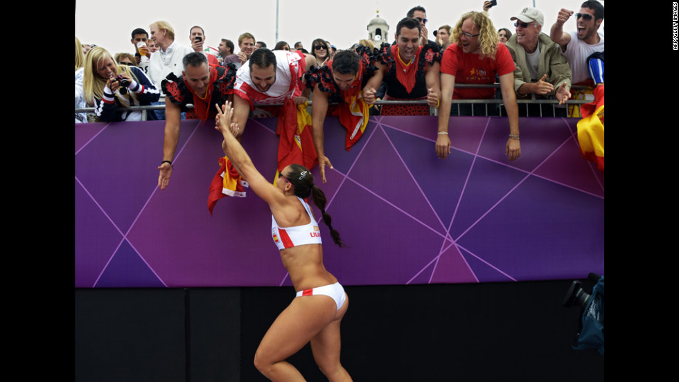 Spain's Liliana Fernandez celebrates with fans after her team's beach volleyball preliminary match against Argentina. Spain won 2-0.