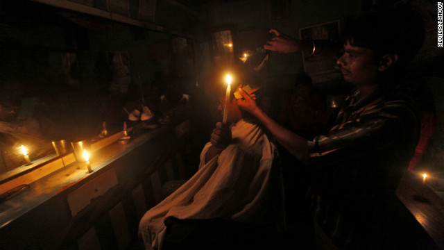 Image #: 18800045    A customer holds a candle as he gets his haircut at a barber's shop during a power-cut in Kolkata July 31, 2012. Grids supplying electricity to half of India's 1.2 billion people collapsed on Tuesday, trapping coal miners, stranding train travellers and plunging hospitals into darkness in the second major blackout in as many days. REUTERS/Rupak De Chowdhuri (INDIA - Tags: ENERGY SOCIETY TPX IMAGES OF THE DAY)       REUTERS /RUPAK DE CHOWDHURI /LANDOV