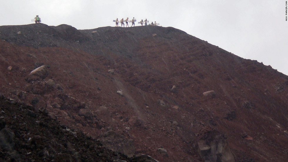 Surfers carry their wooden boards along the volcano's ridge.