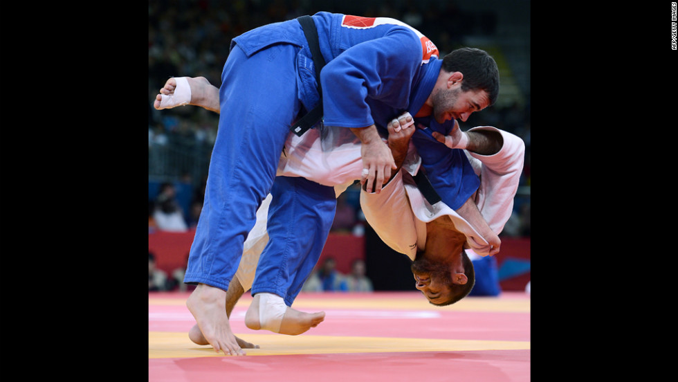 Travis Stevens, in white, of the United States tries to take down Slovenia's Aljaz Sedej during the men's under 81-kilogram judo contest match Tuesday.