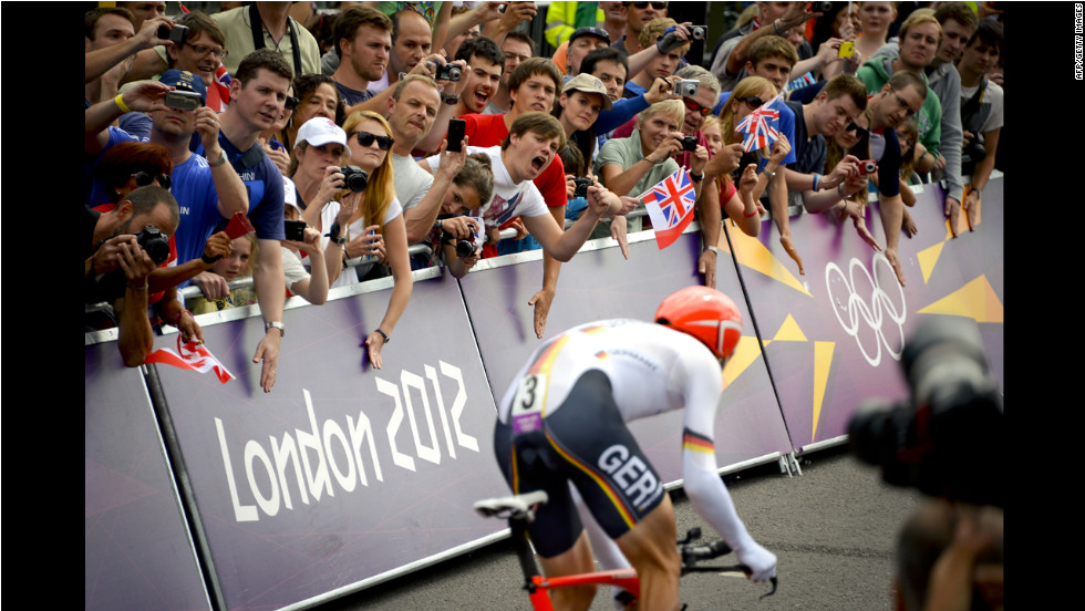The crowds cheer for German silver medalist Tony Martin as he exits the gate of Hampton Palace to start the men's individual time trial road cycling event.