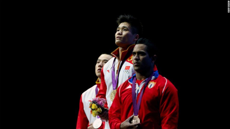 Left to right: Haojie Lu of China (silver), Xiaojun Lu of China (gold) and Ivan Cambar Rodriguez of Cuba (bronze) stand on the podium during the medal ceremony for men's 77-kilogram weightlifting event.