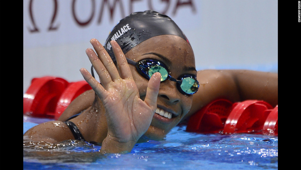 Arianna Vanderpool-Wallace of the Bahamas waves to the crowd after the women's 100-meter freestyle heats Wednesday.