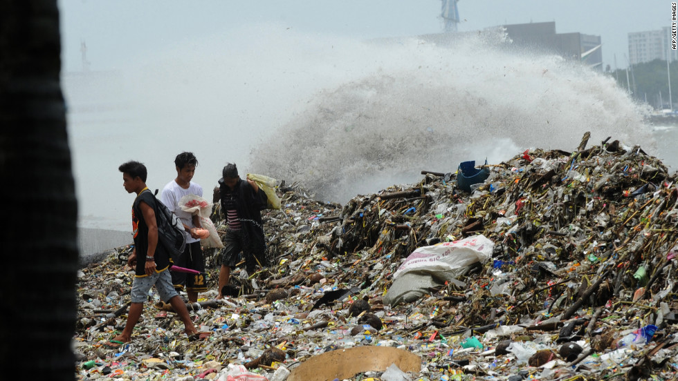 People collect recyclable material from debris washed ashore in Manila on Wednesday, August 1, after heavy rain from Typhoon Saola.