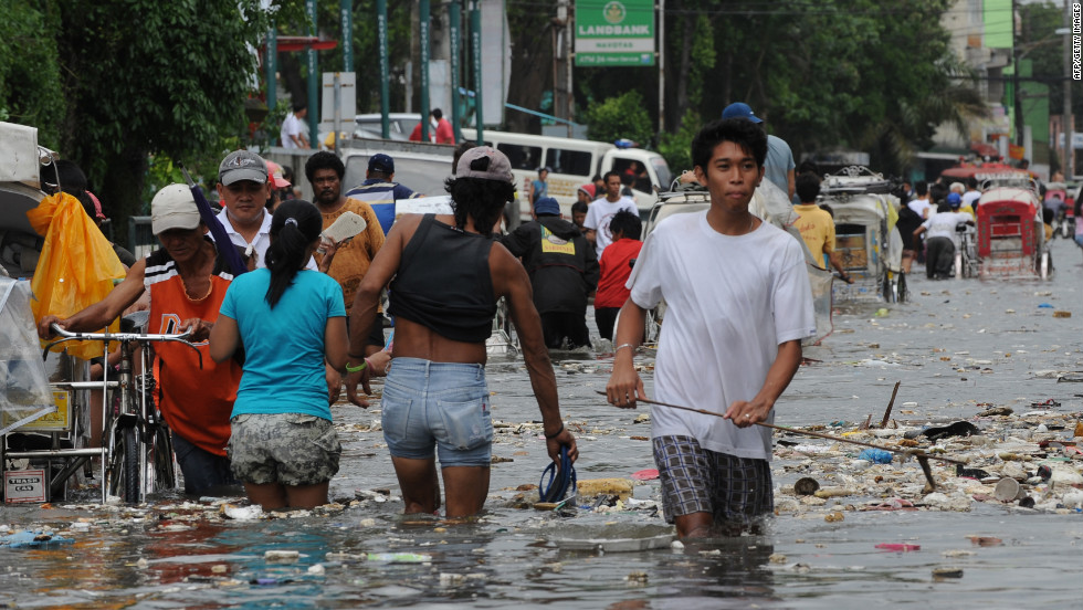 Residents wade through a flooded street filled with trash in Navotas.