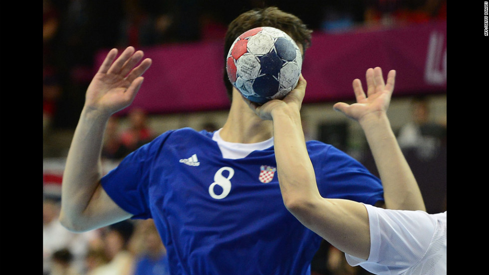 Croatia's Marko Kopljar disappears behind the ball during a men's preliminary handball match between Croatia and Hungary.