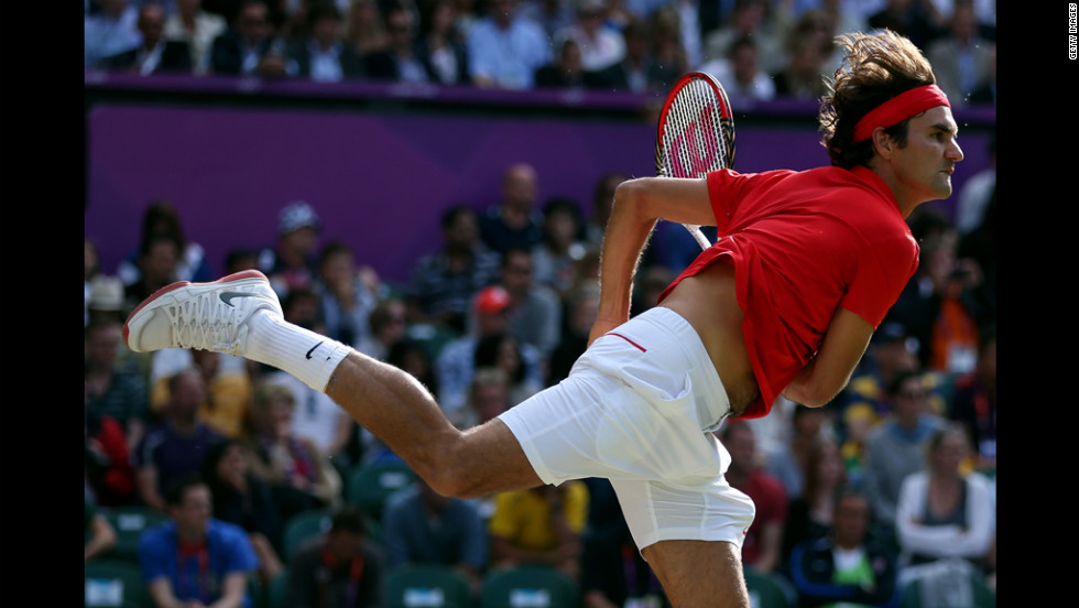 Roger Federer of Switzerland serves the ball to John Isner of the United States during the quarter-final of men's singles tennis.