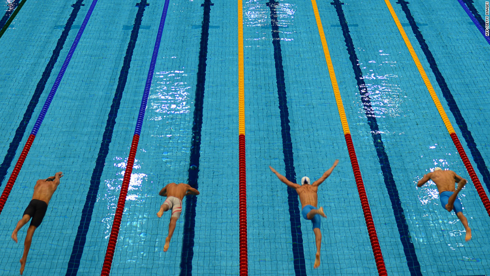 Competitors dive into the pool at the start of the men's 50-meter freestyle heat.