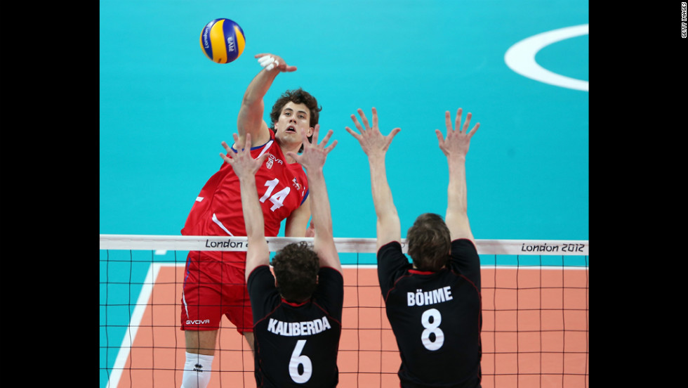 Aleksandar Atanasijevic of Serbia spikes the ball against Denys Kaliberda and Marcus Bohme of Germany.