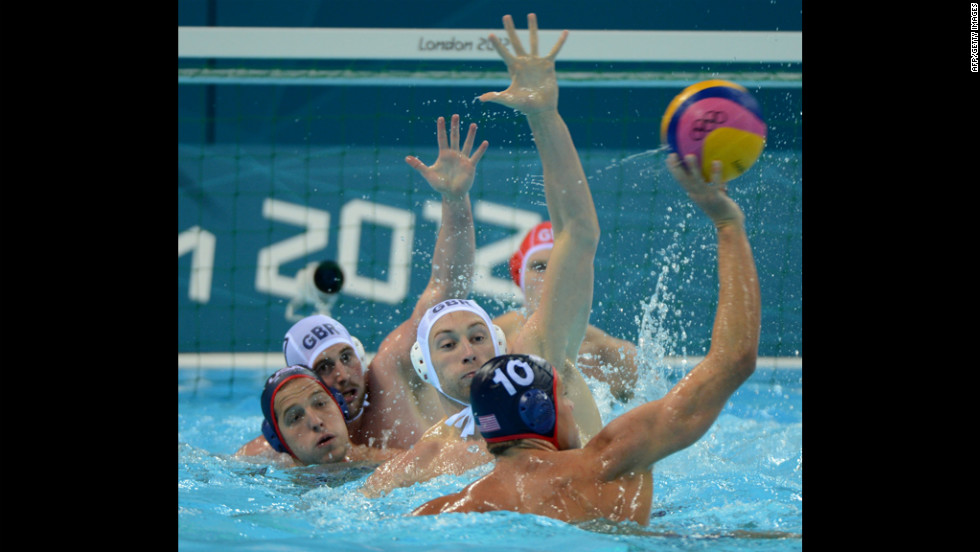 Great Britain's Rob Parker, center, competes with Tim Hutten, right, of the United States in the men's water polo preliminary match. The U.S. team won 7-13.<br />