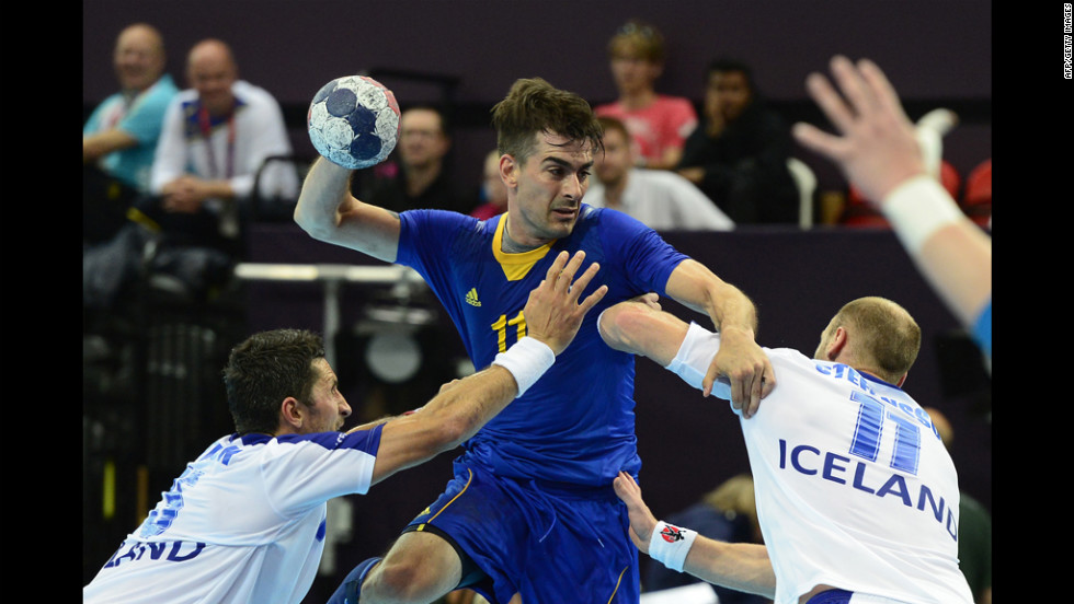 Sweden's center back Dalibor Doder, center, vies with Icelandic players during the men's preliminary group A handball match.