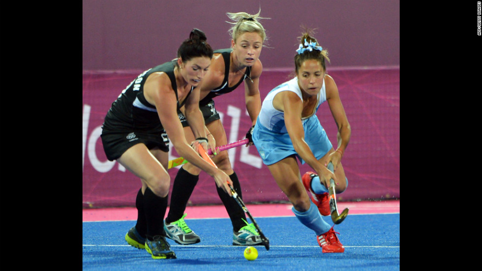 Ella Gunson, left, and Anita Punt, center, of New Zealand challenge Rocio Sanchez Moccia, right, of Argentina during the women's hockey preliminary round match.