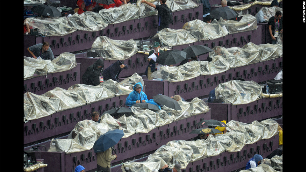 Journalists try to keep their equipment dry with rain covers at the Olympic Stadium.