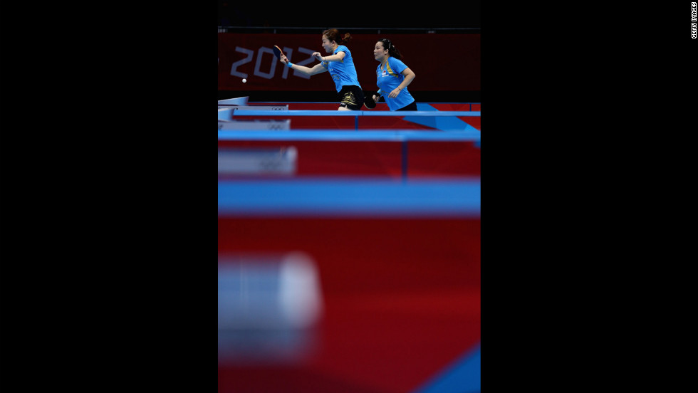 Yuegu Wang, left, and Jiawei Li of Singapore face off against Polish competitors during a first-round match in women's team table tennis.