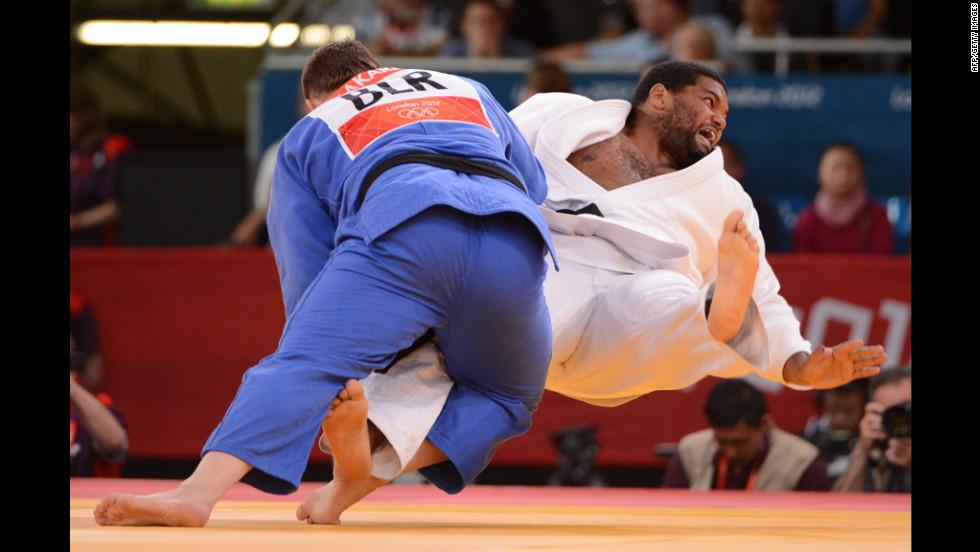 Ihar Makarau, left, of Belarus competes with Cuba's Oscar Brayson during the men's over 100-kilogram judo repechage match.