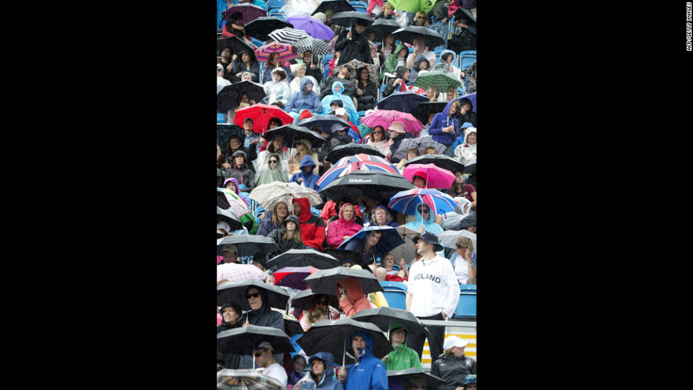 Spectators take cover during the dressage preliminaries at Greenwich Park in London.