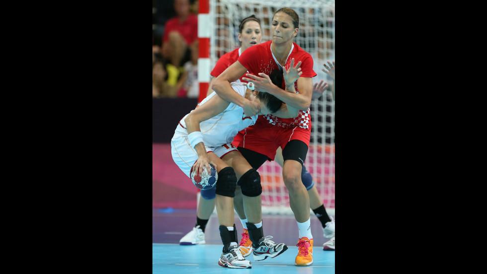 Croatia's Andrea Penezic, right,  grabs the face of Bojana Popovic of Montenegro during the women's handball preliminaries.