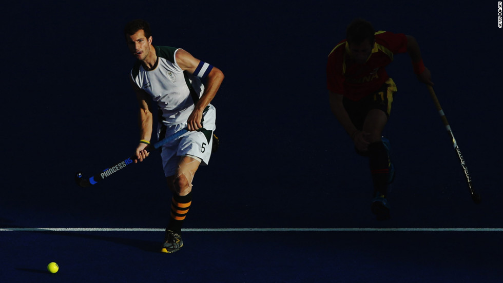 South Africa's captain Austin Smith, left, advances the ball forward with Roc Oliva of Spain in pursuit during the men's hockey match.