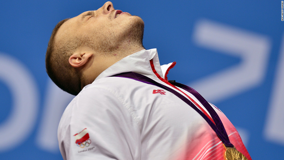 Poland's Adrian Edward Zielinski poses on the podium with his gold medal after winning the men's 85 kilogram group A weightlifting event.