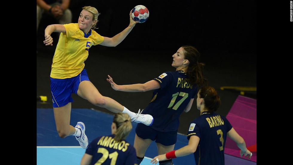 Sweden's pivot Hanna Fogelstrom, left, jumps to shoot during the women's preliminary group B handball match against Spain.