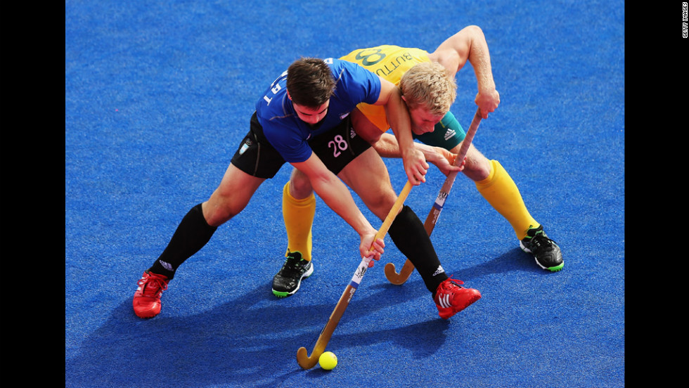 Gonzalo Peillat of Argentina battles with Matthew Butturini of Australia during a men's hockey preliminary match.