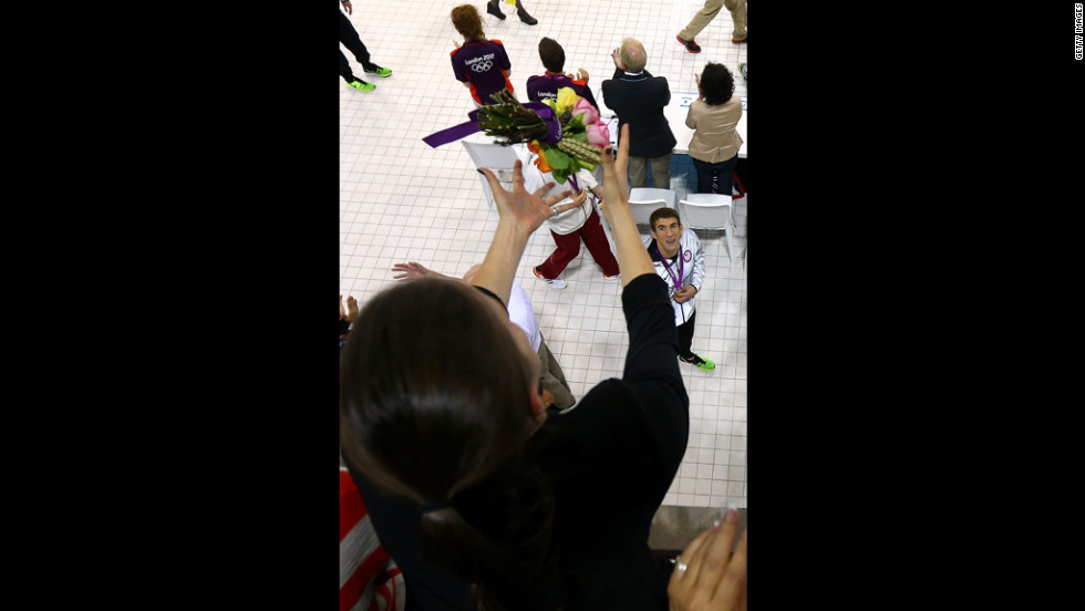 Michael Phelps throws his flowers to his sister Hilary Phelps after the medal ceremony in the men's 200-meter individual medley final.