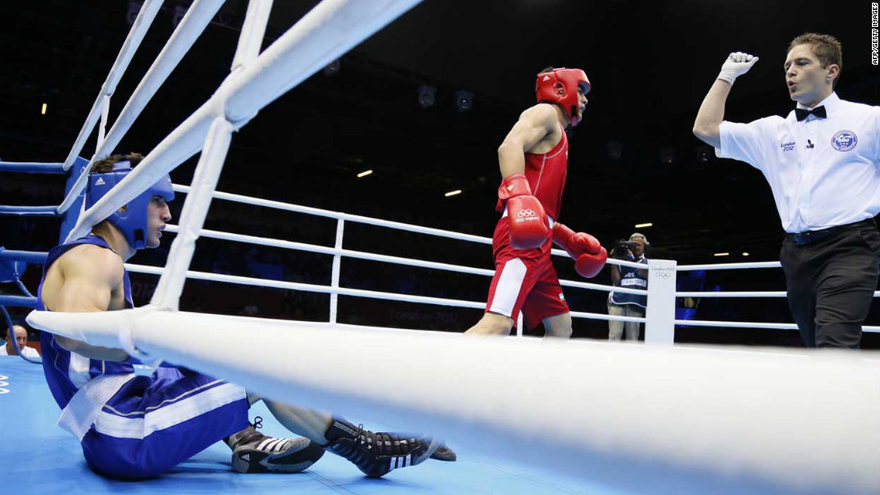 Yakup Sener, left, of Turkey is counted after being knocked down by Uktamjon Rahmonov, center, of Uzbekistan during the round of 16 light-welterweight (64 kilogram) match. Rahmonov was awarded a 16-8 points decision.