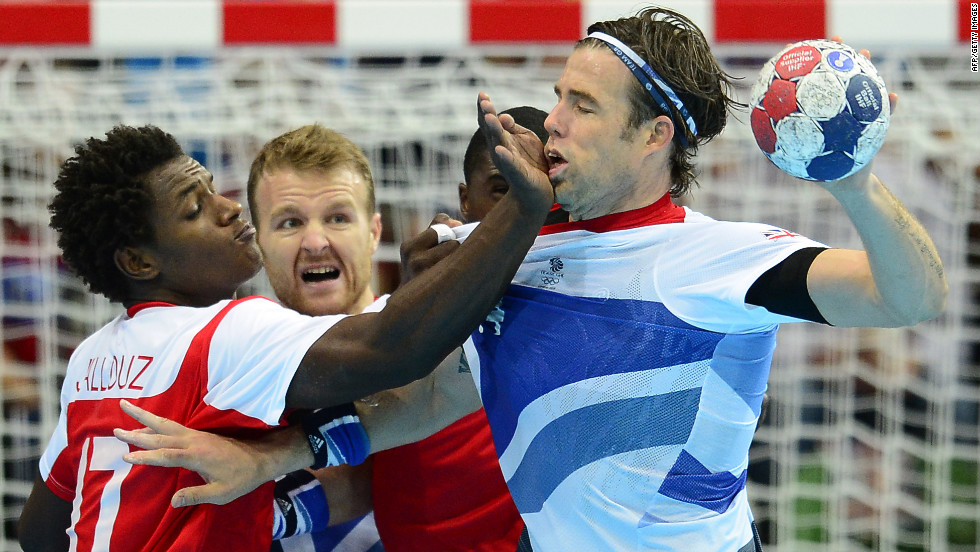 Britain's rightback Steven Larsson, right, tries to take a shot as Tunisia's leftback Wael Jallouz blocks during the men's preliminary Group A handball match.
