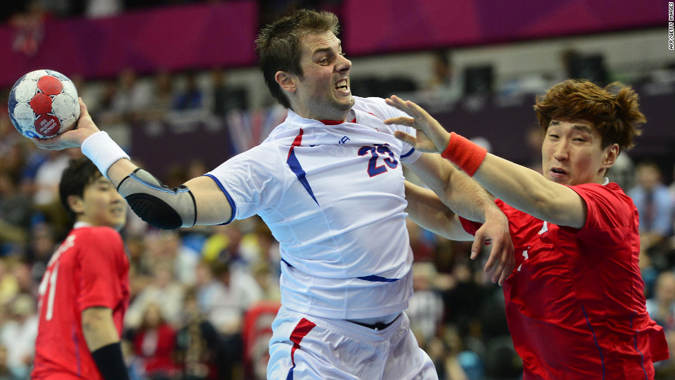 Serbia's left back Momir Rnic, left, jumps to shoot during a men's preliminary handball match against South Korea.